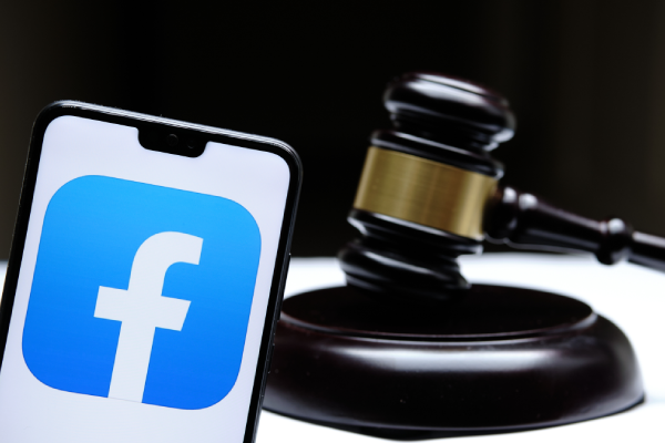 Facebook logo on iphone with a gavel and soundblock in the background.